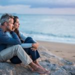 Couple-sitting-together-on-rock-by-expansive-sea-sky-vista-representing-serenity-from-long-term-recovery