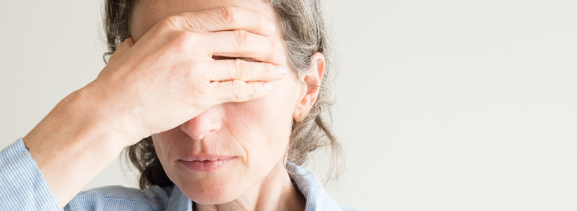woman-with-hand-on-forehead-with-chronic-pain-raleigh-cary-nc